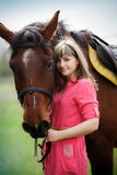 Bella ragazza con un cavallo marrone in parco immagini stock libere da diritti