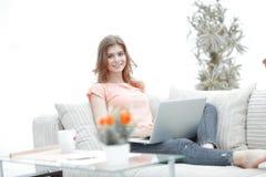 Bella ragazza con un computer portatile che si siede sullo strato Fotografie Stock
