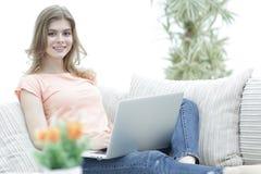 Bella ragazza con un computer portatile che si siede sullo strato Immagini Stock