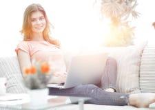 Bella ragazza con un computer portatile che si siede sullo strato Fotografia Stock Libera da Diritti