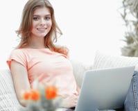Bella ragazza con un computer portatile che si siede sullo strato Immagine Stock Libera da Diritti