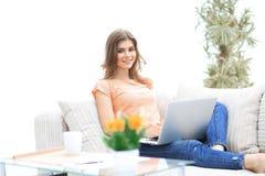 Bella ragazza con un computer portatile che si siede sullo strato Fotografia Stock