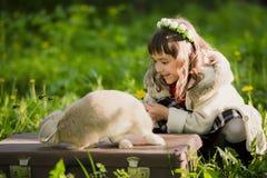 Bella ragazza con un coniglio nel legno Immagini Stock
