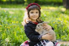 Bella ragazza con un coniglio nel legno Immagine Stock