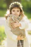 Bella ragazza con un coniglio nel legno Immagini Stock Libere da Diritti