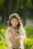 Bella ragazza con un coniglio nel legno Fotografie Stock
