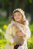Bella ragazza con un coniglio nel legno Fotografia Stock Libera da Diritti