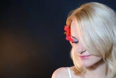 Bella ragazza con un fiore rosso in suoi capelli Immagini Stock Libere da Diritti