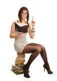 Bella ragazza con un libro che si siede su un mucchio dei libri Immagine Stock Libera da Diritti