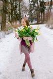 Bella ragazza con un mazzo dei tulipani bianchi e gialli nel parco fotografia stock libera da diritti