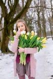 Bella ragazza con un mazzo dei tulipani bianchi e gialli nel parco fotografie stock libere da diritti