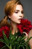 Bella ragazza con un mazzo delle peonie Modello con un trucco delicato Fronte di bellezza immagine stock