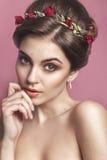 Bella ragazza con un ornamento floreale in suoi capelli Bella donna che tocca il suo fronte Concetto di cura di pelle e della gio immagine stock libera da diritti