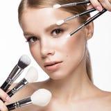 Bella ragazza con un trucco naturale leggero, spazzole per i cosmetici e manicure francese Fronte di bellezza Fotografia Stock