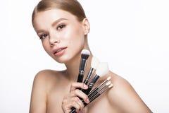 Bella ragazza con un trucco naturale leggero, spazzole per i cosmetici e manicure francese Fronte di bellezza Immagini Stock