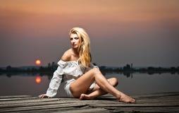Bella ragazza con una camicia bianca sul pilastro al tramonto Immagine Stock