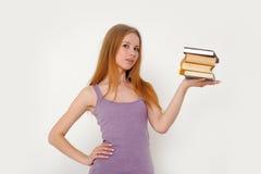 Bella ragazza con una pila di libri Fotografia Stock