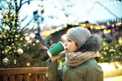 Bella ragazza con una tazza della bevanda calda al mercato di Natale a Mosca immagini stock