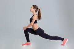 Bella ragazza concentrata di forma fisica che fa allungando esercizio Fotografia Stock