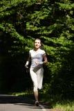 Bella ragazza corrente Corridore femminile che pareggia durante l'allenamento all'aperto sulla traccia in parco o in foresta Immagini Stock Libere da Diritti