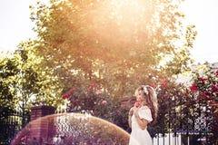 Bella ragazza dai capelli lunghi in vestito bianco lungo che posa vicino ai cespugli di rose al sole immagine stock libera da diritti