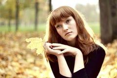 Bella ragazza dai capelli rossi che si siede da solo fotografie stock