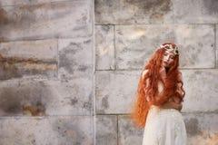Bella ragazza dai capelli rossi con capelli ricci lunghi nella sposa, in un vestito lungo dal pizzo Una bellezza naturale Fotografia Stock Libera da Diritti