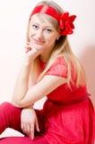 Bella ragazza degli occhi azzurri nel rosso divertendosi delicatamente sorridere & esame della macchina fotografica piacevolmente Fotografie Stock