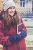 Bella ragazza dei pantaloni a vita bassa con il libro in sue mani Immagine Stock