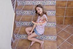 Bella ragazza del bambino che mangia anguria sulle scale a casa Amore della famiglia ed aria aperta di stile di vita fotografia stock libera da diritti