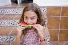 Bella ragazza del bambino che mangia anguria sulle scale a casa Amore della famiglia ed aria aperta di stile di vita immagine stock libera da diritti