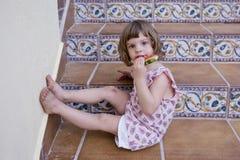 Bella ragazza del bambino che mangia anguria sulle scale a casa Amore della famiglia ed aria aperta di stile di vita immagini stock libere da diritti
