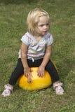 Bella ragazza del bambino divertendosi con l'agricoltura sulla toppa organica della zucca Immagini Stock Libere da Diritti