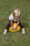 Bella ragazza del bambino divertendosi con l'agricoltura sulla toppa organica della zucca Immagini Stock