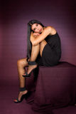 Bella ragazza del brunette in vestito nero che propone dentro Immagine Stock Libera da Diritti