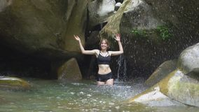 Bella ragazza del movimento lento che spruzza sull'acqua a mano nel lago della montagna in foresta tropicale verde con la piccola stock footage