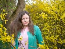 Bella ragazza del ritratto all'aperto in rivestimento verde fra l'albero giallo del fiore Immagini Stock Libere da Diritti