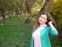 Bella ragazza del ritratto all'aperto in rivestimento verde fra l'albero giallo del fiore Fotografia Stock Libera da Diritti