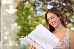 Bella ragazza dell'adolescente che studia leggendo un taccuino all'aperto Fotografia Stock