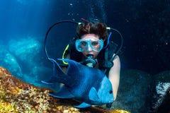 Bella ragazza dell'operatore subacqueo di Latina mentre toccando un pesce fotografia stock libera da diritti