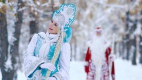 Bella ragazza della neve nella priorità alta che gioca con i suoi capelli e padre Frost nei precedenti archivi video