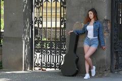 Bella ragazza della testarossa nella via con una chitarra nel caso fotografie stock