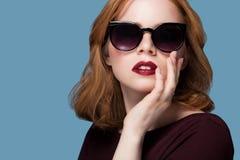 Bella ragazza della testarossa in un trucco luminoso del rossetto rosso marrone rossiccio della blusa in occhiali da sole neri su Immagine Stock