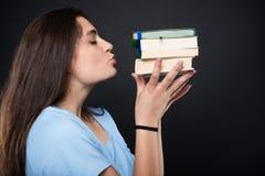 Bella ragazza dello studente che bacia i suoi libri Immagine Stock