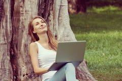 Bella ragazza dello studente che lavora al suo computer portatile all'aperto al giorno soleggiato Fotografie Stock Libere da Diritti