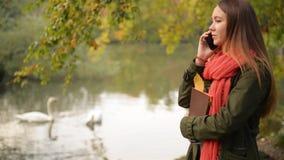 Bella ragazza dello studente che parla sul telefono cellulare nella caduta Donna di Autumn Caucasian che ha conversazione dello s stock footage