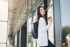 Bella ragazza dello studente con lo zaino ed il caffè Immagine Stock
