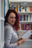 Bella ragazza dello studente della testarossa felice gentile leggendo un libro i Fotografia Stock Libera da Diritti