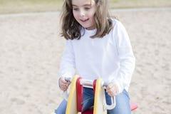 Bella ragazza di 5 anni che gioca fuori su un campo da giuoco Fotografia Stock Libera da Diritti
