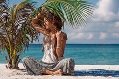 Bella ragazza di boho che si siede sotto la giovane palma sulla spiaggia Fotografia Stock
